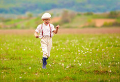 Laufendes blühendes Feld des aufgeregten netten Jungen, Frühlingslandschaft stockfotografie