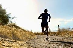 Laufendes Cross Country-Training des vorderen jungen Sportmannes des Schattenbildes bei Sommersonnenuntergang Stockfotos