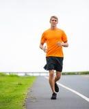 Laufendes draußen rütteln des athletischen Mannes Lizenzfreie Stockfotografie