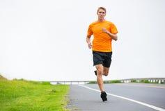 Laufendes draußen rütteln des athletischen Mannes Stockbild