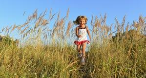 Laufendes glückliches kleines Mädchen Lizenzfreies Stockfoto