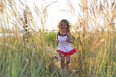 Laufendes glückliches kleines Mädchen Stockfoto