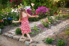 Laufendes glückliches Mädchen in einem blühenden Garten Lizenzfreie Stockbilder