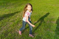 Laufendes kleines Mädchen im Park, das Kind hat Spaß, spielt und lässt auf dem grünen Rasen laufen lizenzfreie stockbilder