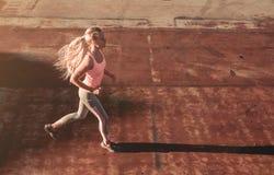 Laufendes Mädchen auf Straße lizenzfreie stockbilder