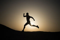 Laufendes Mannschattenbild am Sonnenunterganghimmel Stockbilder