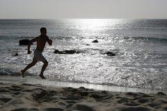 Laufendes oder rüttelndes Training des jungen Mannes auf dem Strand Stockbild