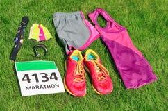 Laufschuhe, Marathonlaufschellfischzahl, Läufergang und Energiegele auf Grashintergrund, Sportwettbewerb, Eignung Stockfoto