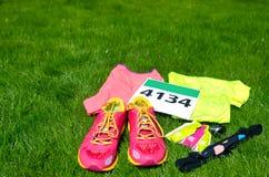 Laufschuhe, Marathonlaufschellfischzahl, Läufergang und Energiegele auf Grashintergrund, Sportwettbewerb, Eignung Stockfotografie