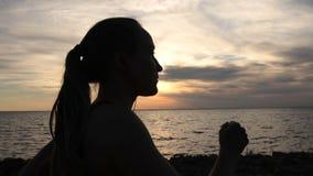 Laufsitzfrau, die auf dem Strand bei Sonnenuntergang rüttelt stock video