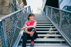 Laugh is the best sport. Happy and beautiful middle aged woman sitting on metallic stairs relaxing before running outdoors holding a water bottle Royalty Free Stock Images