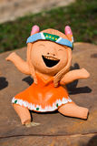 Laugh Doll. The Ceramic Laugh Doll sit on the Rock Royalty Free Stock Image
