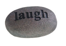 Laugh engraved on stone. Word, laugh engraved on rounded stone, isolated on white background Royalty Free Stock Image