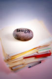 Laugh off workload. A pile of folders of work with a stone on top that reads 'laugh Royalty Free Stock Images
