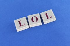 Laugh Out Loud. The acronym LOL spelled out with tiles on a blue background Stock Images