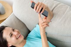 Laugh woman couch phone idle lifestyle addiction. Laughing woman laying on the couch using phone. idle lifestyle and mobile devices addiction royalty free stock images