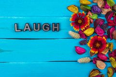 Laugh word on blue wood with flower. Laugh word on old blue color wood with flower and dried flower royalty free stock photography