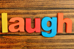 Laugh word on table. Laugh word on wooden table Royalty Free Stock Photography