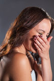 Laugh. Young female laughing covering her mouth with her hand Stock Photo