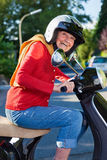 Laughing active senior woman on a scooter. Laughing active senior woman in casual jeans and a helmet riding on a scooter down the street stock image