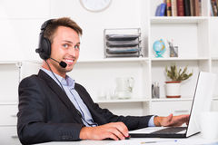 Laughing adult man talking on headset at office. Laughing adult man talking on headset at company office Stock Photos