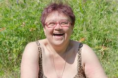 Laughing adult woman sunbathes in the grass under the bright summer sun stock photos
