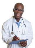 Laughing african american doctor with clipboard Royalty Free Stock Photos