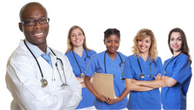Laughing african american doctor with crossed arms and group of. International nurses on isolated white background Royalty Free Stock Photography