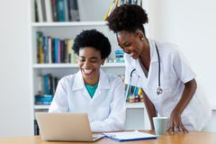 Laughing african american female doctor with young nurse royalty free stock photography