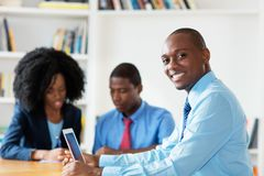 Laughing african american financial advisor with business team royalty free stock image