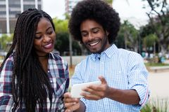 Laughing african american hipster man showing pictures at phone Stock Photo
