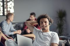 Laughing african american hipster software developer at computer at office of startup company.  royalty free stock images