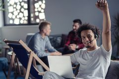 Laughing african american hipster software developer at computer at office of startup company.  stock photography