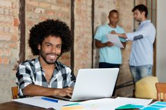 Laughing african american hipster software developer at computer. At office of startup company stock photo