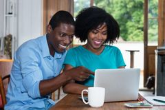 Laughing african american love couple indoors at computer Stock Photos