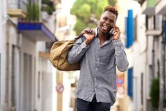 Laughing african american male traveler walking and talking on mobile phone. Portrait of laughing young african american male traveler walking outside and Stock Photos