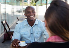 Laughing african american man flirting with caucasian woman. Laughing african american men flirting with caucasian women in a restaurant outdoor in the summer royalty free stock images