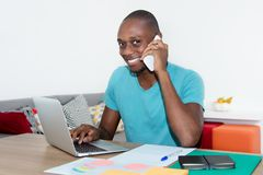 Laughing african american man working with computer and speaking. At phone at home office Royalty Free Stock Images
