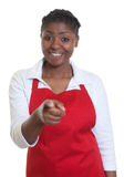 Laughing african american waitress pointing at camera. On an isolated white background for cut out Stock Photos