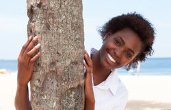 Laughing african american woman behind a tree Royalty Free Stock Photo