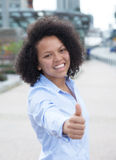 Laughing african american woman in the city showing thumb Royalty Free Stock Images