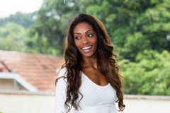 Laughing african american woman with long hair. Outdoors in the summer Royalty Free Stock Image