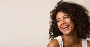 Laughing african-american woman looking away on light background. Copy space stock photo