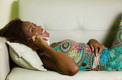 Laughing african american woman speaking at phone on sofa Stock Photo