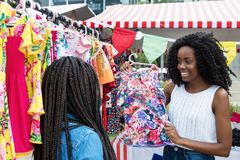 African american woman presenting colorful clothes at market. Laughing african american women presenting colorful clothes to client outdoors at typical Stock Photography