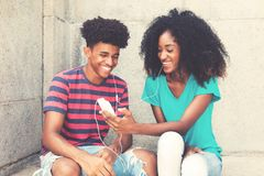 Laughing african american young adult couple loves music. Outdoors in vintage retro look royalty free stock photo