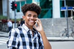 Laughing african american young adult at mobile phone. Outdoor in the city Stock Images