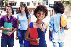 Laughing african american young adult woman with students in city. Laughing african american young adult women with students in city in summer royalty free stock image