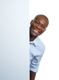Laughing african businessman behind a signboard Stock Photo