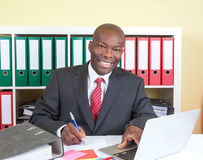 Laughing african businessman writing a message Stock Images